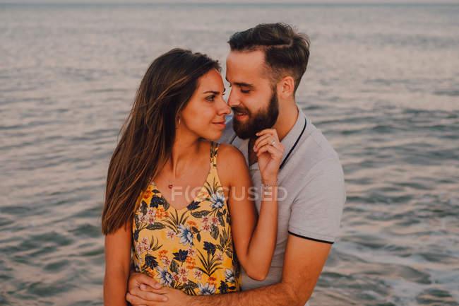 Любящий мужчина обнимает очаровательную женщину на берегу моря — стоковое фото