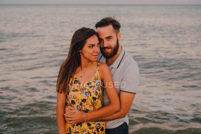 Verliebter Mann umarmt charmante Frau sanft am Meer — Stockfoto