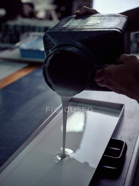 Bookbinder versando colla nello stampo da bottiglia quadrata — Foto stock
