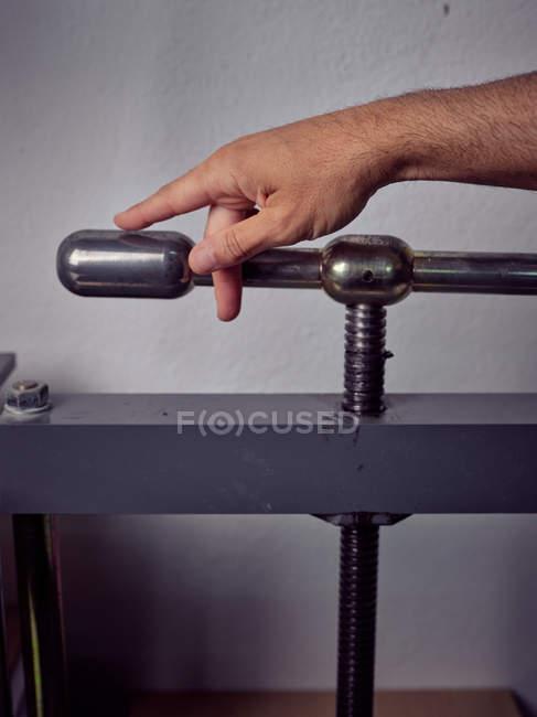 Main d'ouvrier méconnaissable utilisant la machine pressante dans l'imprimerie — Photo de stock