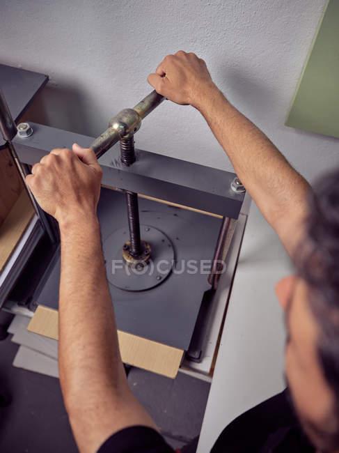 Ouvrier méconnaissable utilisant la machine pressante dans l'imprimerie — Photo de stock