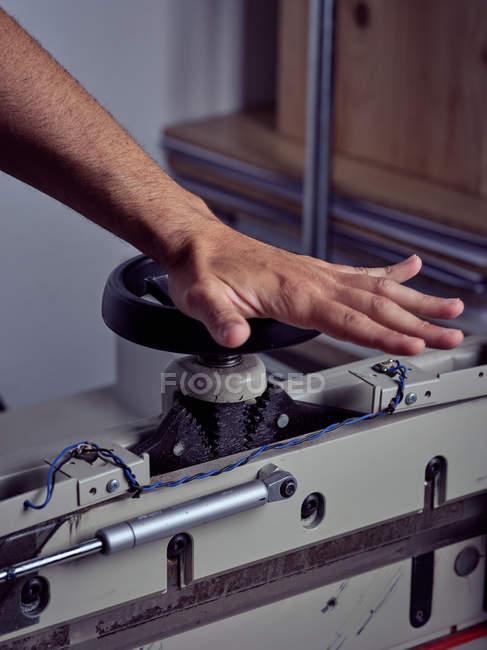 Mano di competente artigiano rotante maniglia ruota della macchina da stampa vincolante su sfondo sfocato — Foto stock
