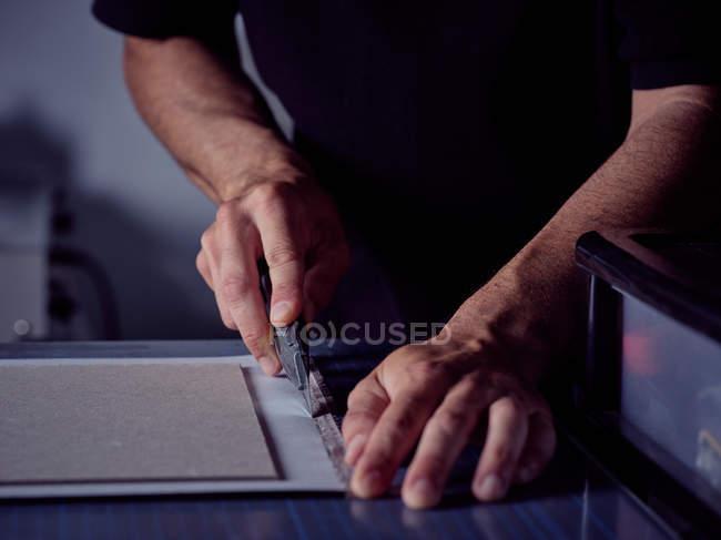 Руки рабочего режущего листа с канцелярским ножом на поверхности — стоковое фото