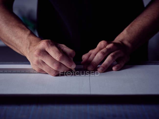 Mani di bookbinder facendo markup con la matita a pagina — Foto stock