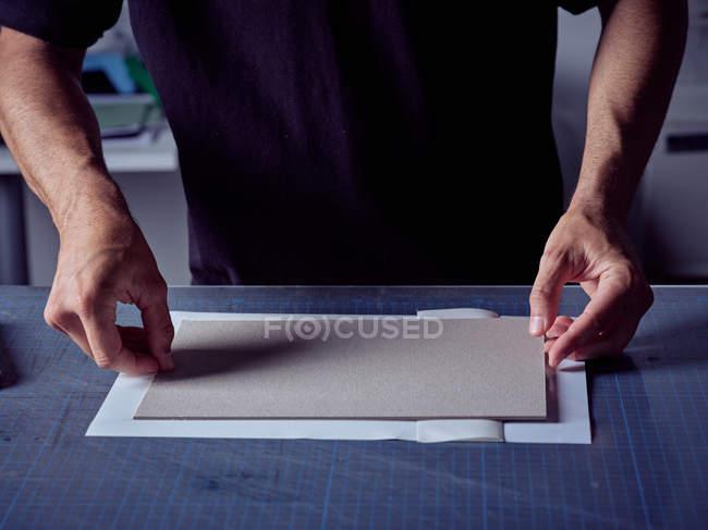 Buchmacher Faltpapier über Deckbrett — Stockfoto