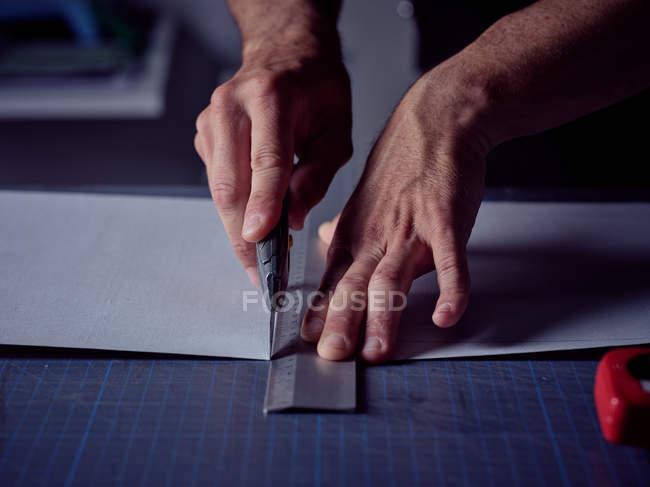 Lenzuolo da taglio operaio con coltello da cancelleria in superficie — Foto stock