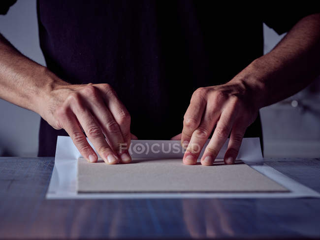 Craftsman hands making book hardback by wrapping cardboard sheet in white paper — Stock Photo