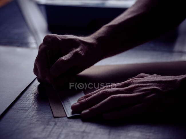 Hands of bookbinder making markup with pencil on page — Stock Photo