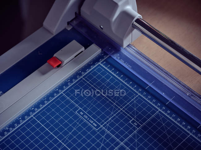 Close-up of blue graph manual paper cutting machine with size lines on wooden table — Stock Photo