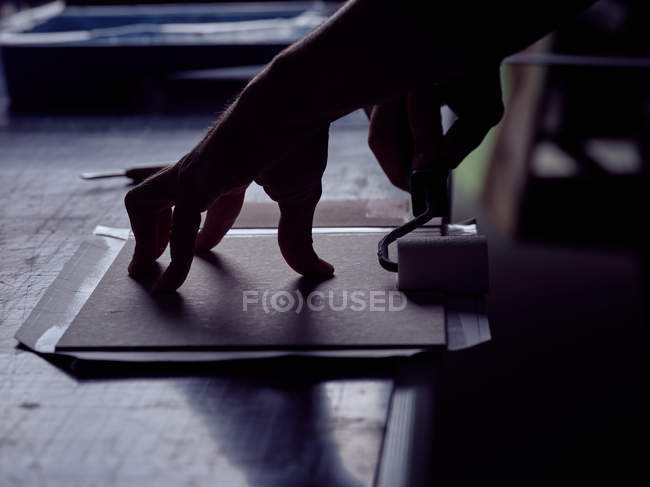 Руки bookbinder склеивания книги в твердом переплете с рулоном — стоковое фото