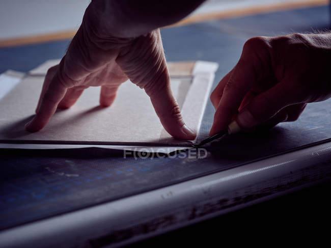 Mani di foglio di taglio operaio con coltello cancelleria sulla superficie — Foto stock
