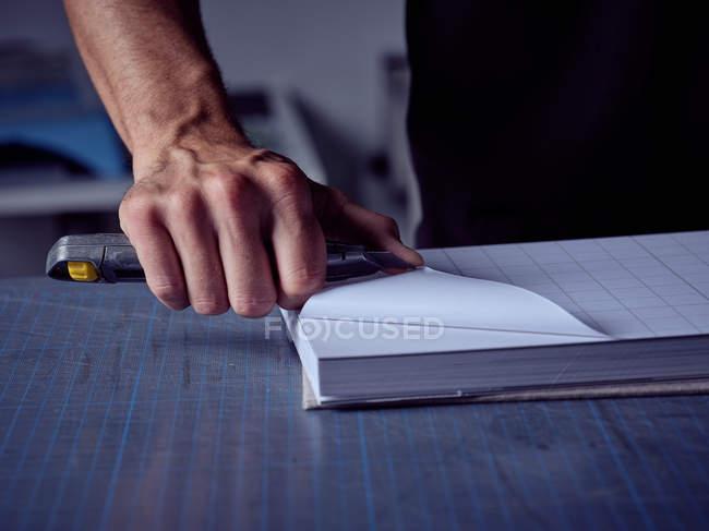 Рука переплётчика стоя за столом и вырезая клетчатые страницы книги ножом в мастерской — стоковое фото