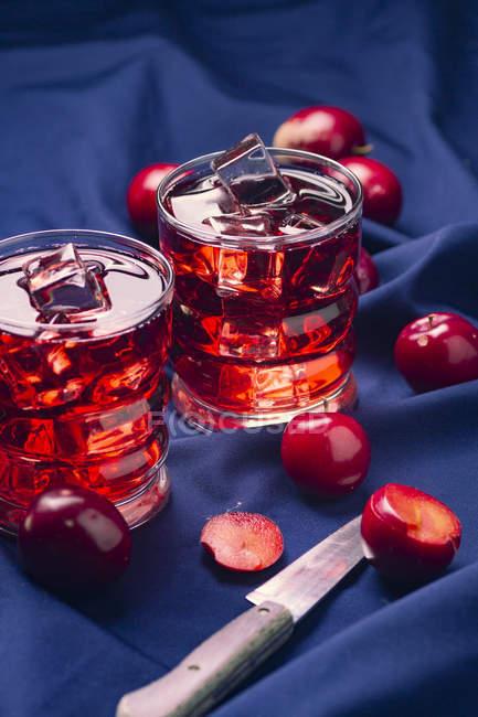 Bebida vermelha perto de frutas frescas em pano azul — Fotografia de Stock