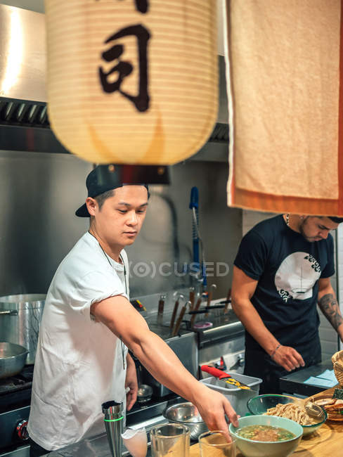 Multiracial men cooking Japanese dish called ramen in Asian restaurant indoors — Stock Photo