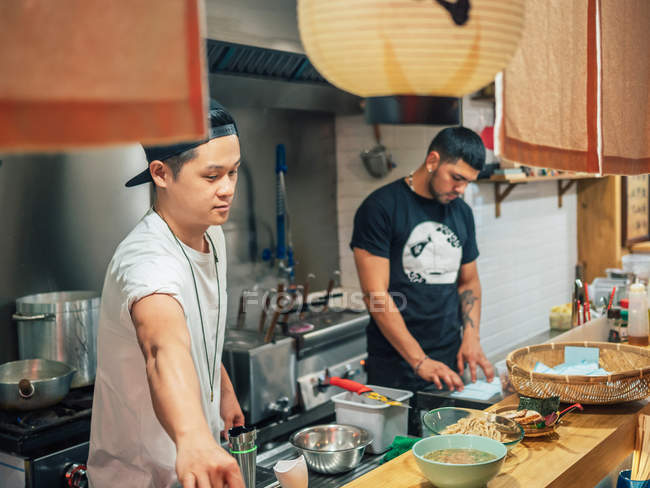 Multiracial men cooking Japanese dish in Asian restaurant indoors — Stock Photo