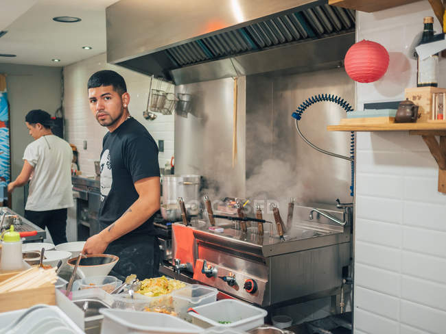 Hombre étnico guapo de pie en la cocina y la elección de ingredientes para el plato japonés llamado ramen - foto de stock
