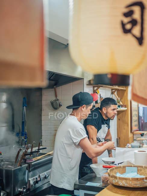 Вид сбоку многорасовых молодых людей приготовления японского блюда называется рамэн в азиатском ресторане и глядя в камеру — стоковое фото