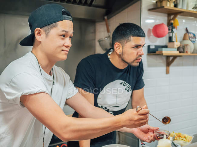 Side view on Asian man offering sauce for fresh cooked Japanese dish ramen and ethnic colleague standing nearby — Stock Photo