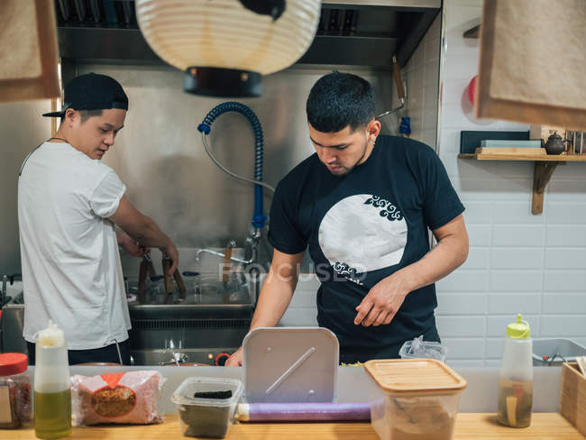 Young multiracial men cooking and serving Japanese dish ramen in Asian bistro — Stock Photo