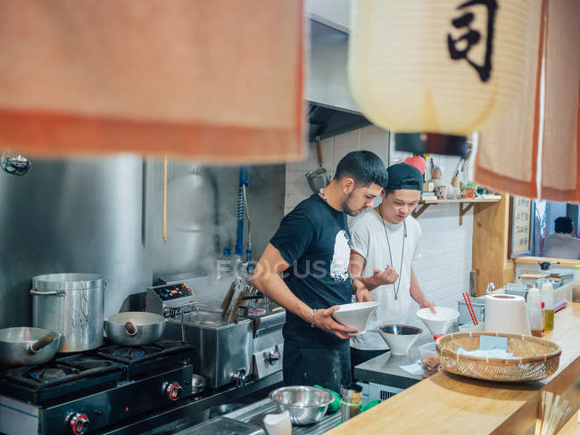 From above of kitchen with young men cooking Japanese dish ramen in oriental restaurant — Stock Photo