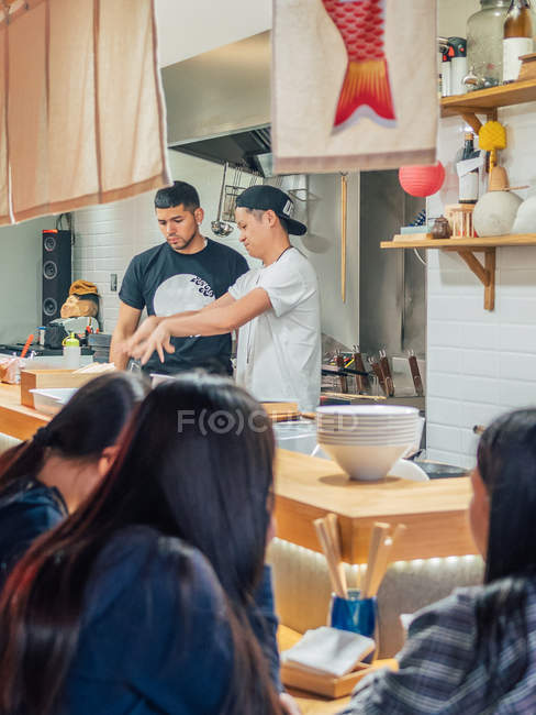 From above kitchen with young men cooking Japanese dish ramen in oriental restaurant — Stock Photo