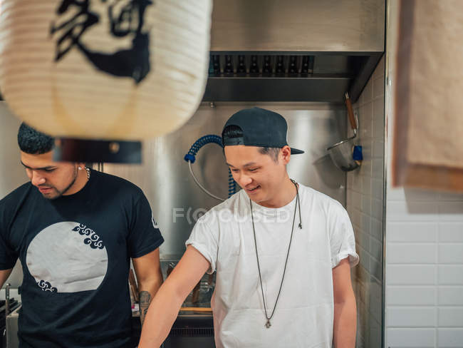 Multiethnic male chefs cooking Asian food in cafe — Stock Photo