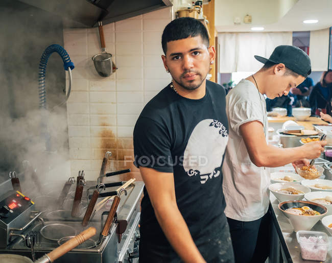 Ethnic man standing and looking in camera while colleague serving bowls with ramen in kitchen — Stock Photo