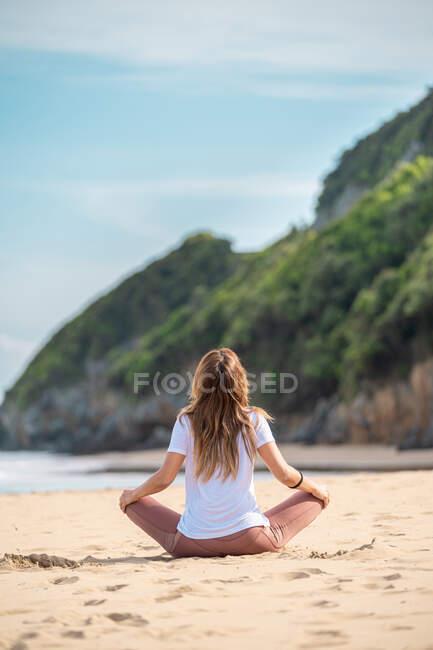 Молодая женщина практикует йогу на пляже — стоковое фото