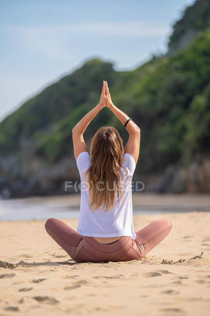 Вид сзади здоровой женщины в костюме, занимающейся йога-асаной на песчаном берегу летом — стоковое фото