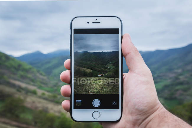 Рука анонимного пользователя, использующего смартфон, чтобы сфотографировать зеленую холмистую местность и деревню в пасмурный день — стоковое фото