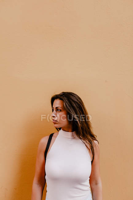 Young woman standing against orange background — Stock Photo