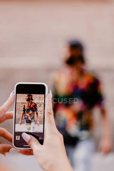 Imagem cortada de mulher tirando foto do moderno hipster barbudo em camisa elegante colorido usando smartphone — Fotografia de Stock