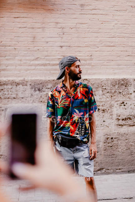 Cropped image of woman taking photo of bearded man — Stock Photo