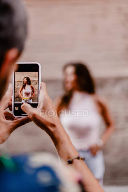 Imagem cortada de homem tirando foto de mulher morena — Fotografia de Stock