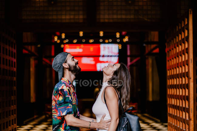 Side view of loving excited man and woman standing opposite and laughing against old town building entrance — Stock Photo