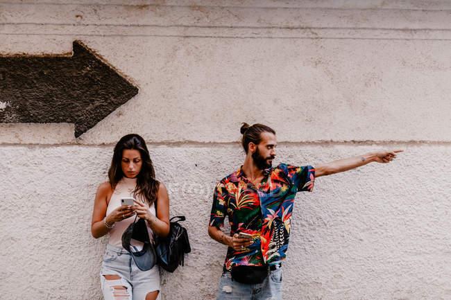 Casal em busca de direção enquanto passeia na rua — Fotografia de Stock