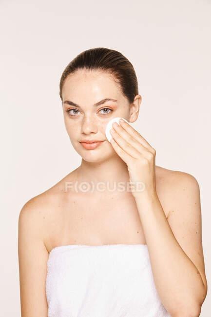Tranquillo tonico femminile applicato su viso radiante con spugna — Foto stock