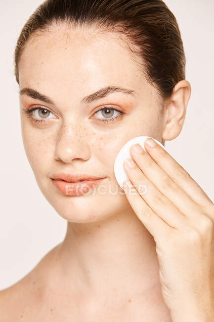 Freckled woman cleansing face skin face with lotion on cotton sponge isolated on white background — Stock Photo
