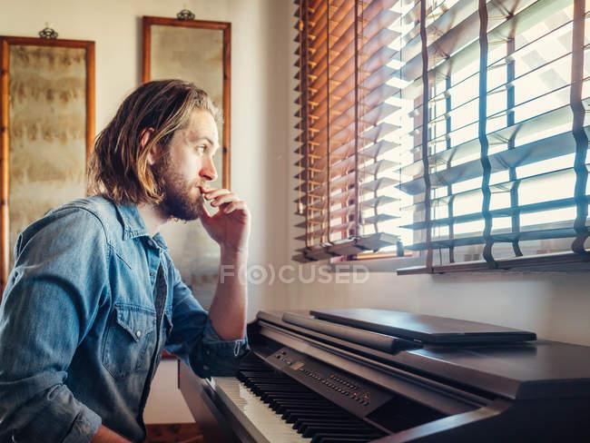 Задумчивый молодой человек смотрит в окно рядом с синтезатором дома — стоковое фото