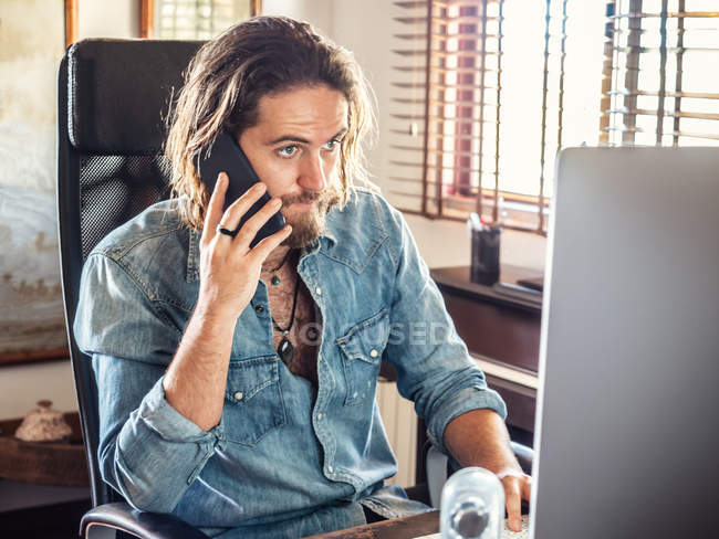 Concentrated man in casual shirt communicating on smartphone while using computer in home office — Stock Photo