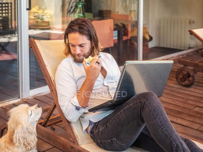 Mann mit Laptop und Apfelkern mit Spaniel-Hund auf Balkon — Stockfoto