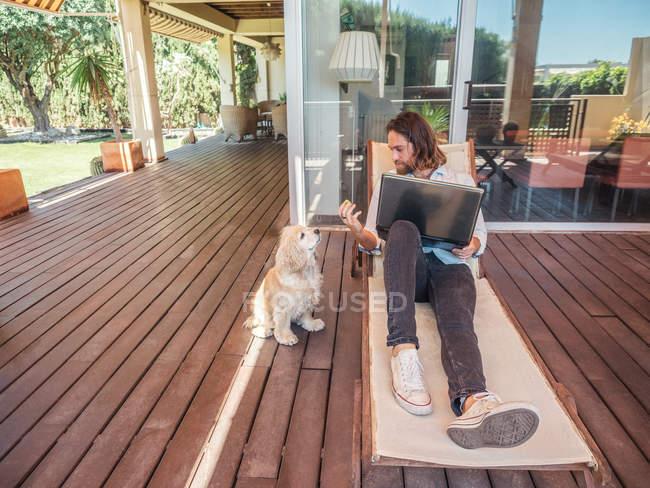 Людина з ноутбуком даючи Apple Core собаку — стокове фото