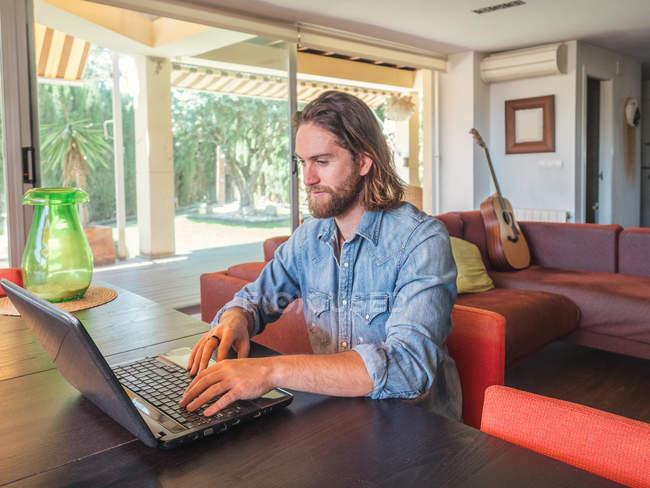 Homem focado trabalhando com computador em apartamento — Fotografia de Stock