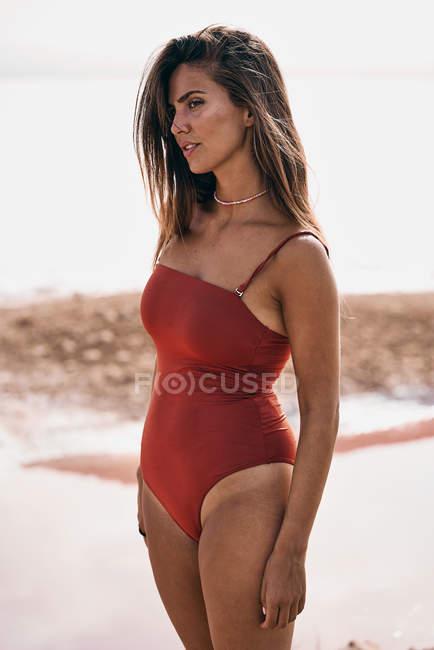 Привабливим жінка в червоному купальнику полюючи на пляжі — стокове фото