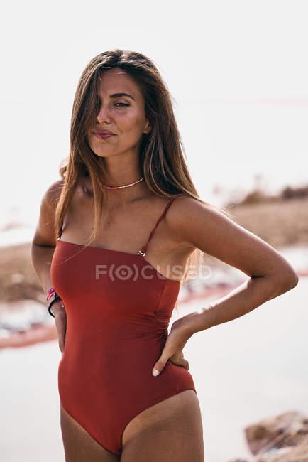 Приваблива жінка в купальнику полюючи на пляжі — стокове фото