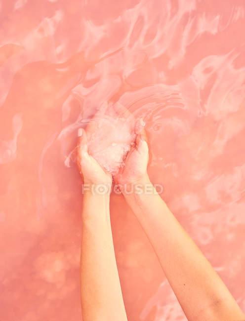 Tenuta femminile guarigione sale mucchio in mano in acqua rosa — Foto stock