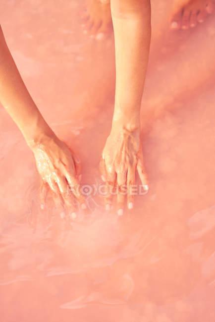 Mani femminili toccano la pila di sale curativa in acqua rosa — Foto stock