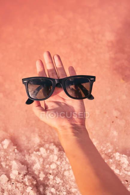 Mão feminina segurando óculos de sol acima da água rosa — Fotografia de Stock
