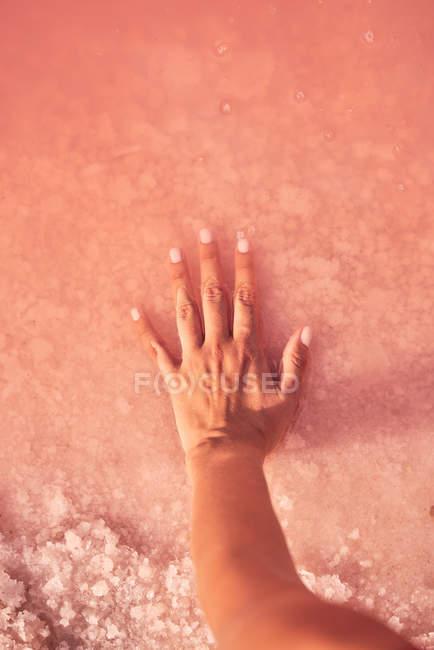 Frauenhand berührt heilenden Salzhaufen in rosa Wasser — Stockfoto