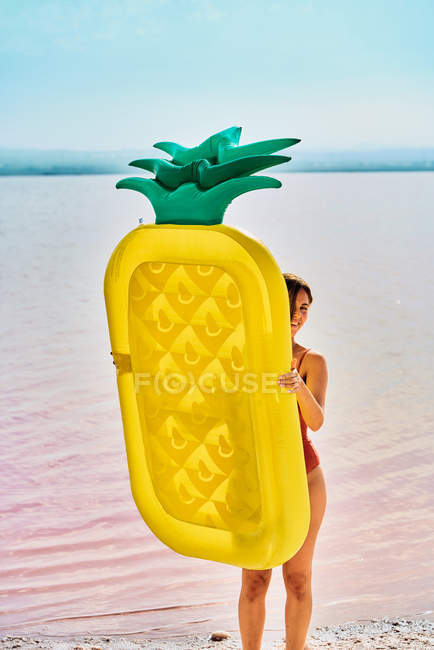 Young woman walking with inflatable mattress on coast in summer — Stock Photo
